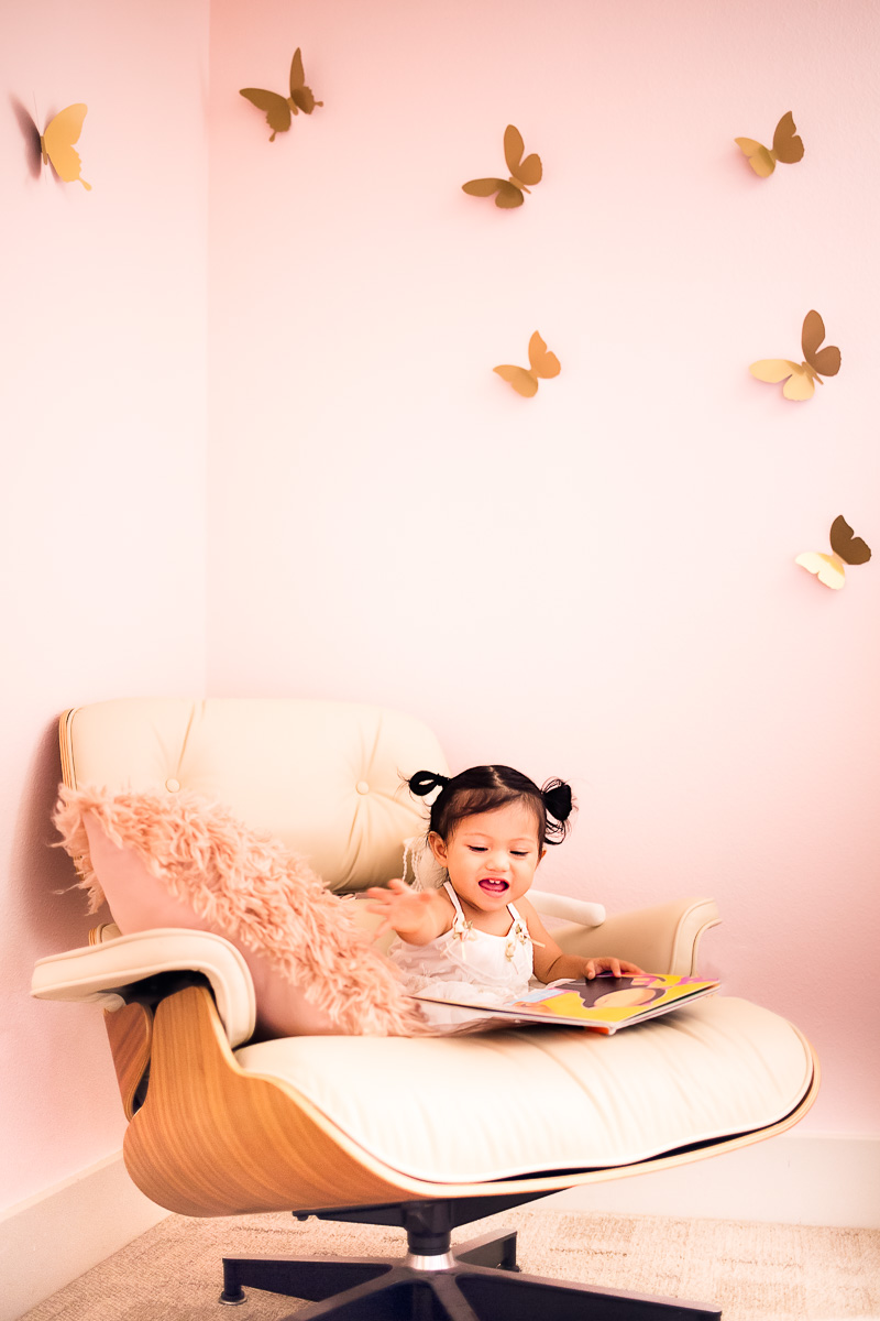toddler girl pink nursery, eames lounge chair reading nook, floating butterflies wall decor