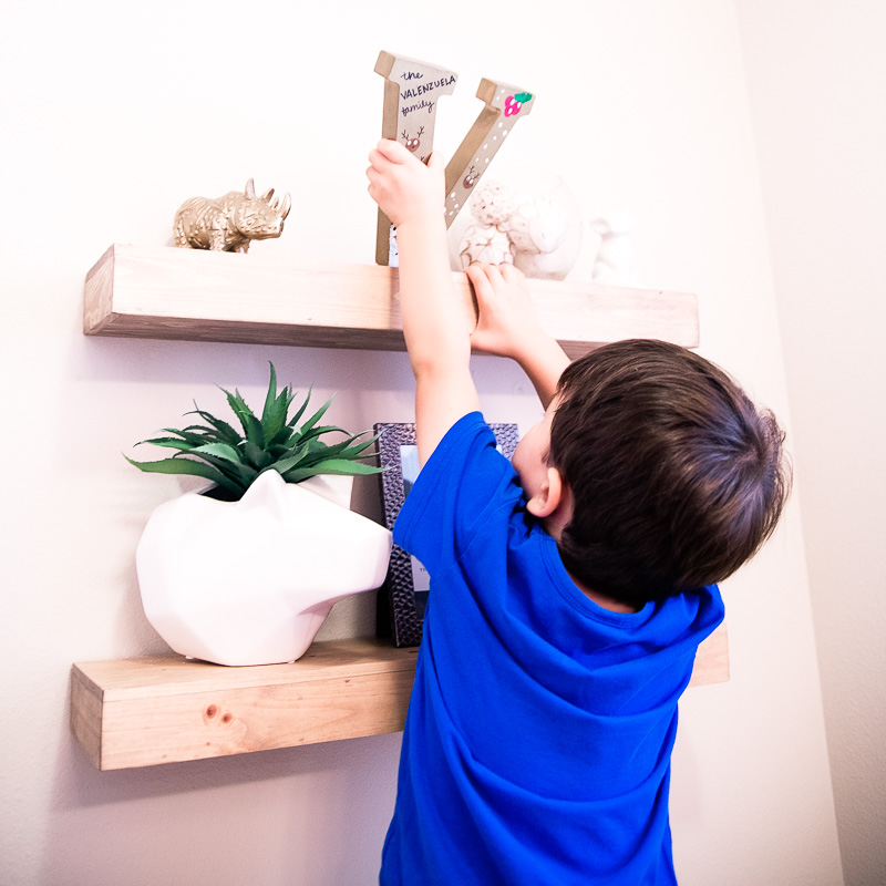 bathroom decor | toddler boy puts finishing touch to shelves