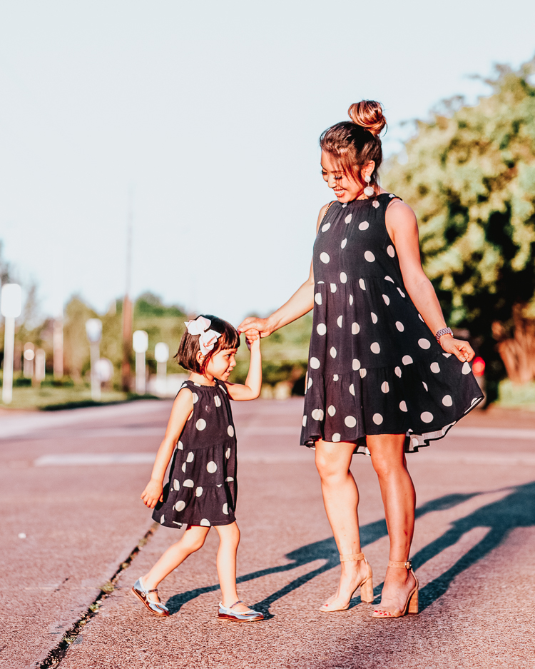 Mommy and Me Outfits featured by top US petite fashion blog Cute & Little; Image of a woman wearing LOFT Dot Tiered Swing Dress, Schutz 'Enida' Cork Sandals, pink pom earrings, Amazon Gucci dupe crossbody bag and her daughter wearing loft littles polka dot navy swing dress.