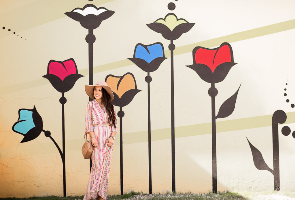 cute & little | popular dallas fashion blog | dallas mural guide | instagram walls | flowers wall | carrollton | Dallas Mural Guide: Top 10 Instagram Walls by popular Dallas blog, Cute and Little: image of a woman standing in front of a flower stalks mural and wearing a striped maxi dress, gold skinny belt, floppy felt hat and hold a Gucci Soho disco bag.