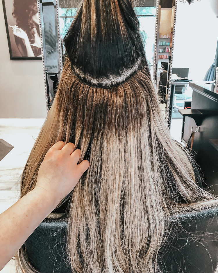 cute & little | popular dallas fashion blog | hand-tied hair extensions before/after faq | Everything You Need To Know About Tie In Hair Extensions by popular Dallas beauty blog, Cute and Little: image of a woman sitting in a salon chair and getting tie in hair extensions.