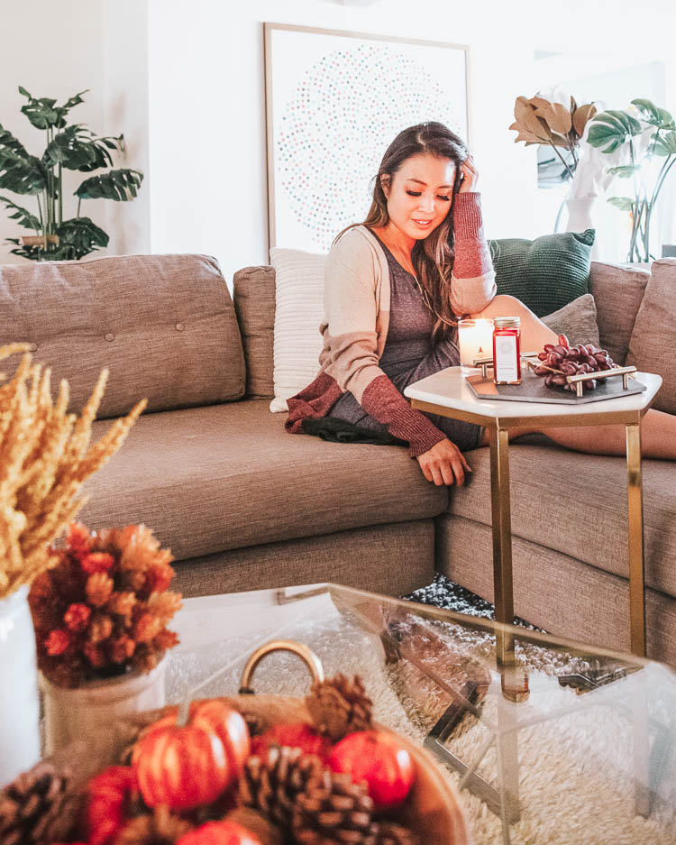 cute & little | popular dallas petite fashion lifestyle blog | how to decorate for fall on a budget | living room decor | How to Get Beautiful Fall Home Decor on a Budget by popular Dallas life and style blog, Cute and Little: image of a woman sitting inside next to a lit Trapp candle.