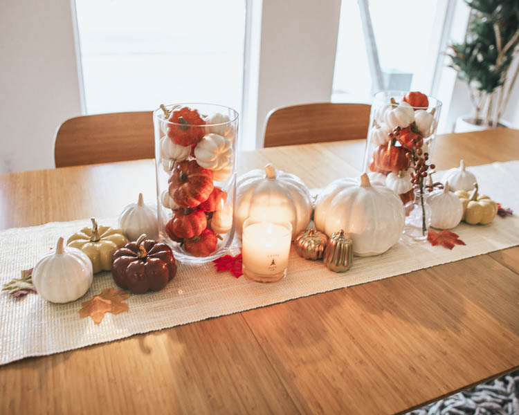 "cute & little | popular dallas petite fashion lifestyle blog | how to decorate for fall on a budget | dining room centerpiece tablescape | How to Get Beautiful Fall Home Decor on a Budget by popular Dallas life and style blog, Cute and Little: image of a table decorated with a West Elm Metallic Laced Runner, Target Hurricane Glass Pillar Candle Holder, Target Decorative Foam Pumpkin Vase Filler, Target ceramic pumpkins, Target cream 3.8"" x 3.3"" Decorative Ceramic Pumpkin, Target 6.7"" x 5.5"" Decorative Ceramic Pumpkin in cream, Trapp candle, and Target gold 2pc Stoneware Pumpkin Salt and Pepper Shaker Set."