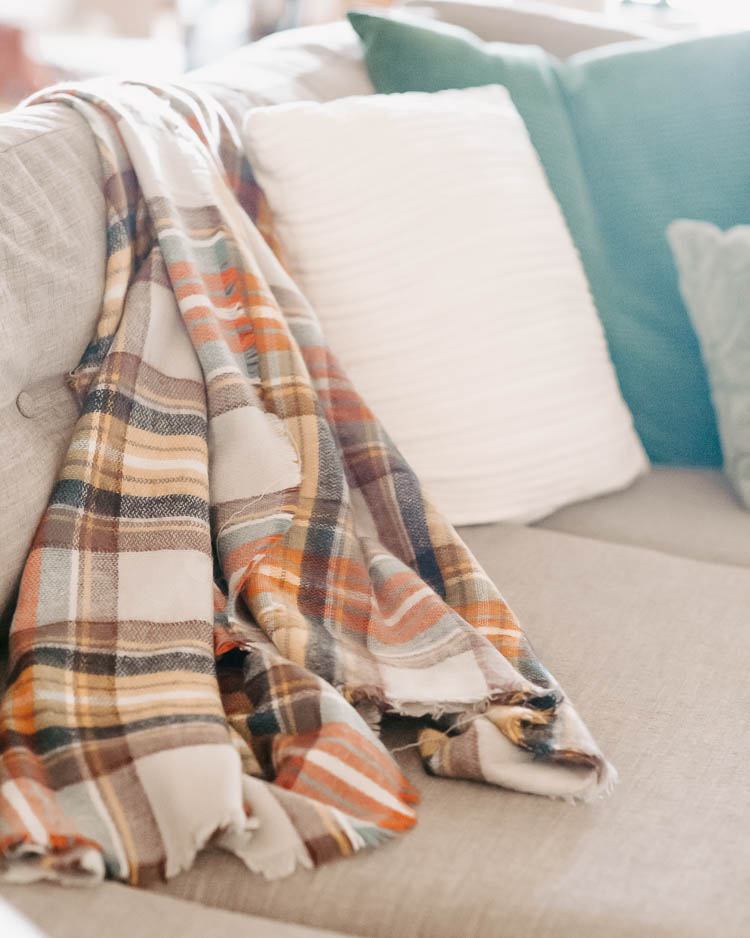 How to Get Beautiful Fall Home Decor on a Budget by popular Dallas life and style blog, Cute and Little: image of a couch decorated with a plaid throw and white and blue pillows.