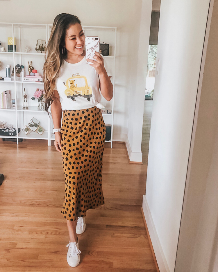 cute & little | august 2019 top sellers | j.crew factory graphic tee, madewell painted spots cheetah leopard midi skirt, white sneakers | August 2019 Top Sellers by popular Dallas petit fashion blog, Cute and Little: image of a woman wearing a Madewell Painted Spots Midi Slip Skirt.