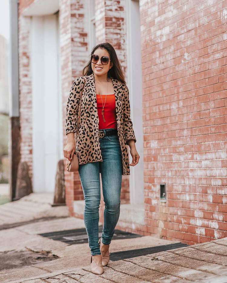 cute & little | dallas petite fashion blog | j.crew leopard sophie blazer, express rust orange bodysuit, express denim perfect jeans | fall outfit | Welcoming Fall In A Statement Leopard Blazer by popular Dallas petite fashion blog, Cute and Little: image of a woman walking outside and wearing a J. Crew Sophie open-front sweater-blazer in leopard, Express bag notification image ITEM ADDED TO YOUR BAG VIEW BAG High Waisted Denim Perfect Leggings, Gucci Thin Leather GG-Buckle Belt, Nordstrom Rack Vince Darlington Flat, and Gucci GG 0106 S- GG0106S Sunglasses 56mm.