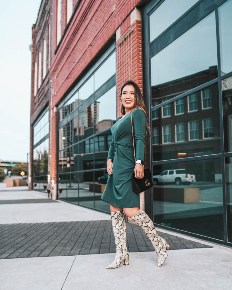 cute & little blog | dallas petite fashion blog | amazon work business casual fall dress, sam edelman hai knee high snakeskin boots | how to wear snakeskin boots | How To Wear Snakeskin Boots by popular Dallas petite fashion blog, Cute and Little: image of a woman in front of brick building and wearing a Lark & Ro Women's Crepe Knit Three Quarter Sleeve Center Twist Dress, Sam Edelman Hai Knee High Boot, Amazon CUIL Quilted Purse Gold Metal Letters Shoulder Bag, ShopBop Madewell Medium Chunky Hoop Earrings, Fitbit Versa, and has her hair curled with a Ulta SinglePass Curl Professional Ceramic Curling Iron.