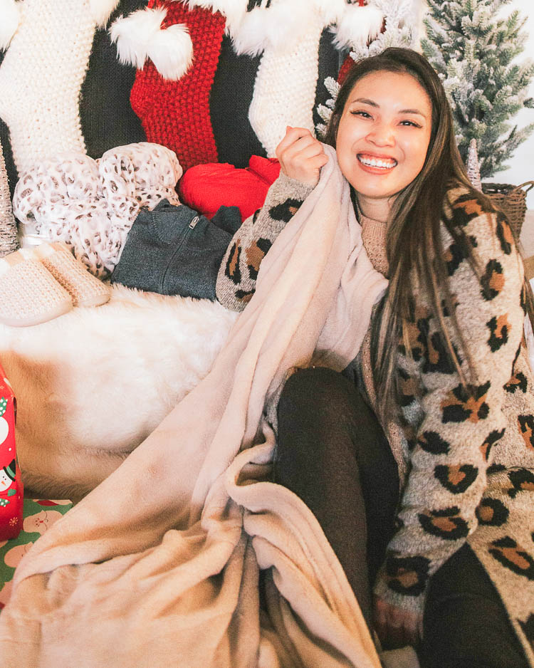 cute & little | dallas petite fashion blog | holiday gift guide cozy ideas | jcpenney budget affordable | heated blanket | Holiday Gift Guide: Cozy Gift Ideas by popular Dallas petite fashion blog, Cute and Little: image of a woman sitting on the floor with a heated blanket and wearing a JcPenney Alyx Womens Long Sleeve Open Front Animal Cardigan, JcPenney St. John's Bay Womens Crew Neck Long Sleeve Pullover Sweater St. John's Bay Womens Crew Neck Long Sleeve Pullover Sweater, and JcPenney a.n.a Womens Mid Rise Legging.