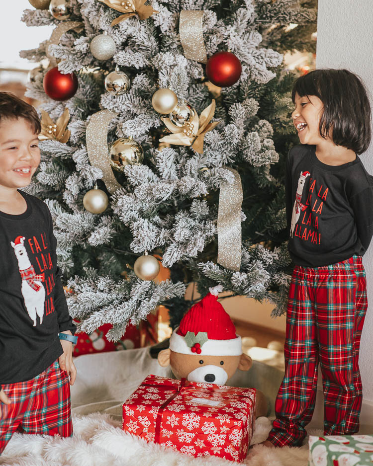cute & little | dallas petite fashion blog | holiday gift guide cozy ideas | jcpenney budget affordable | family matching llama pajamas | Holiday Gift Guide: Cozy Gift Ideas by popular Dallas petite fashion blog, Cute and Little: image of two kids in front of a Christmas tree and wearing matching JcPenney holiday pajama sets.