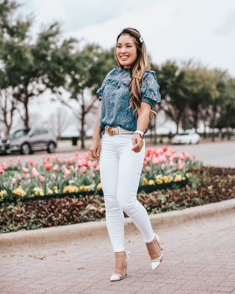 cute & little | dallas petite fashion blog | loft blue vine ruffle puff sleeve blouse, white jeans, justfab prizilla lucite pumps, white gucci belt | business casual spring work outfit | Social Distancing at Home by popular Dallas lifestyle blog, Cute and Little: image a woman walking by some tulips and wearing a Loft VINE RUFFLE PUFF SLEEVE BLOUSE, American Eagle AE NE(X)T LEVEL HIGHEST WAIST JEGGING, Just Fab Prizilla D'orsay Pump, Target Fitbit Versa Lite Smartwatch, Neiman Marcus Gucci GG Marmont Chevron Quilted Leather Flap Wallet on a Chain, and Sephora HUDA BEAUTY Liquid Matte Lipstick.