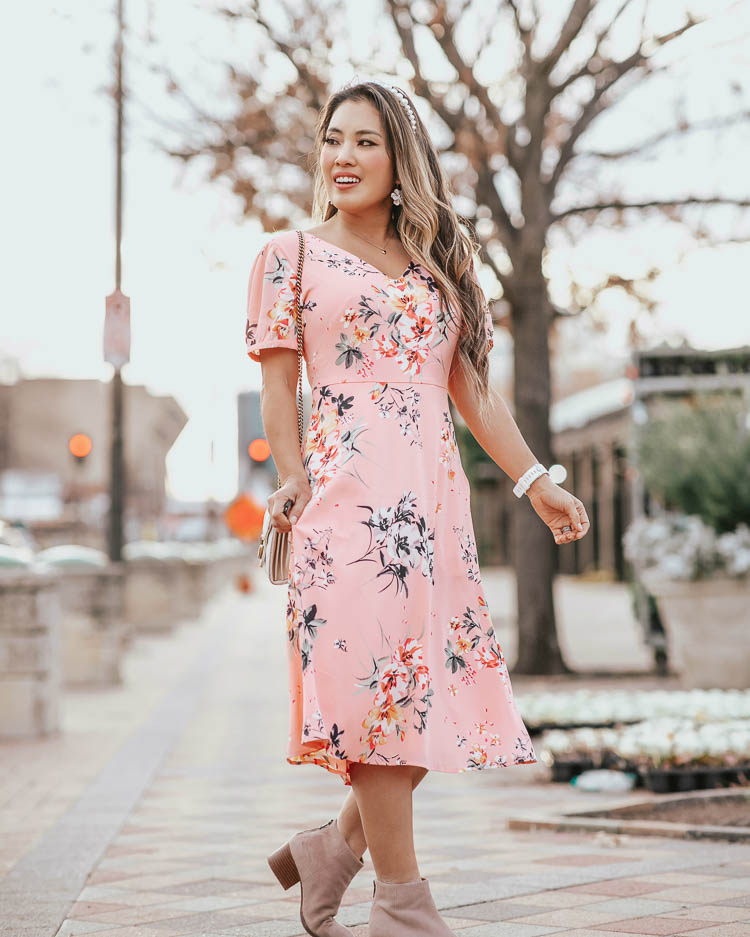 cute & little blog | dallas petite fashion | loft pink floral midi dress | spring outfit | Loft Sale by popular Dallas petite fashion blog, Cute and Little: image of a woman walking down a city street and wearing a Loft FLORAL SMOCKED BACK MIDI DRESS, Loft SEYCHELLES SUEDE FLOODPLAIN BOOTIES, Neiman Marcus GG Marmont Chevron Quilted Leather Flap Wallet on a Chain, Amazon Navachi 18k Gold Plated White Enamel Flower Crystal Az2461e Hoop Earrings, and Amazon WILLBOND pearl headband.