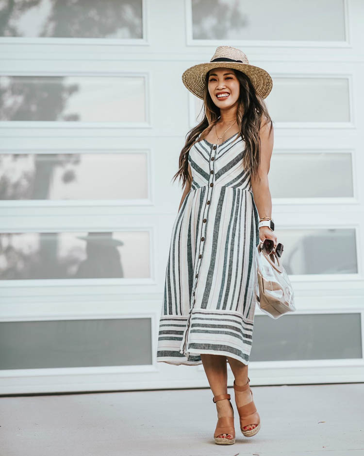 cute & little | target summer dresses | striped midi dress, brixton straw hat | Target Summer Dresses by popular Dallas petite fashion blog, Cute and Little: image of a woman standing outside and wearing a Target Target Universal Thread Button-Front Sun Dress, Treasure & Bond 'Sannibel', Fitbit 'Versa' Lite, Panacea Layered Circle Pendant, Brixton 'Joanna' Straw Hat, Quay 'Backstage' sunglasses, and holding an amazon clear tote bag.