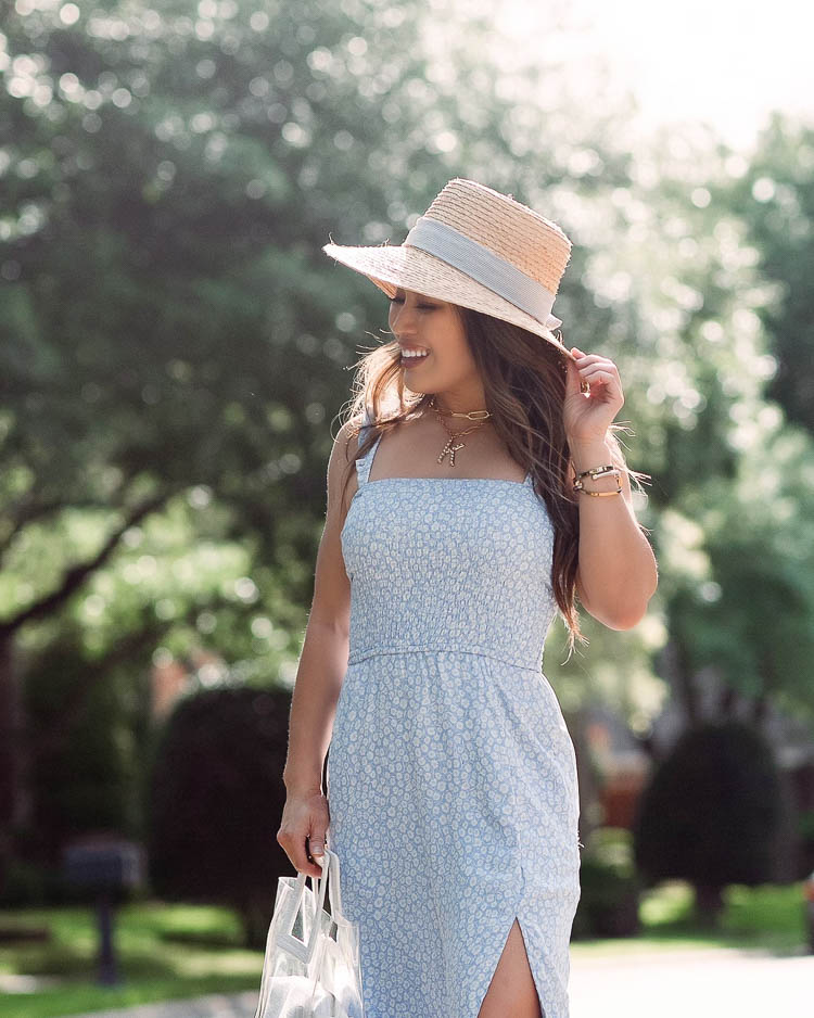 cute & little | dallas petite fashion blog | abercrombie blue smocked midi dress, straw hat, clear tote, white sandals | summer must-have accessories | Summer Outfits by popular Dallas petite fashion blog, Cute and Little: image of a woman wearing a Abercrombie and Fitch Smocked Midi Dress, Steve Madden Greece White Leather Slide Sandals, Revolve Lampshade Hat Hat Attack brand:Hat Attack, DSW CLEAR TOTE, Sequin PEARL INITIAL TALISMAN NECKLACE, and BaubleBar HERA LINK NECKLACE.