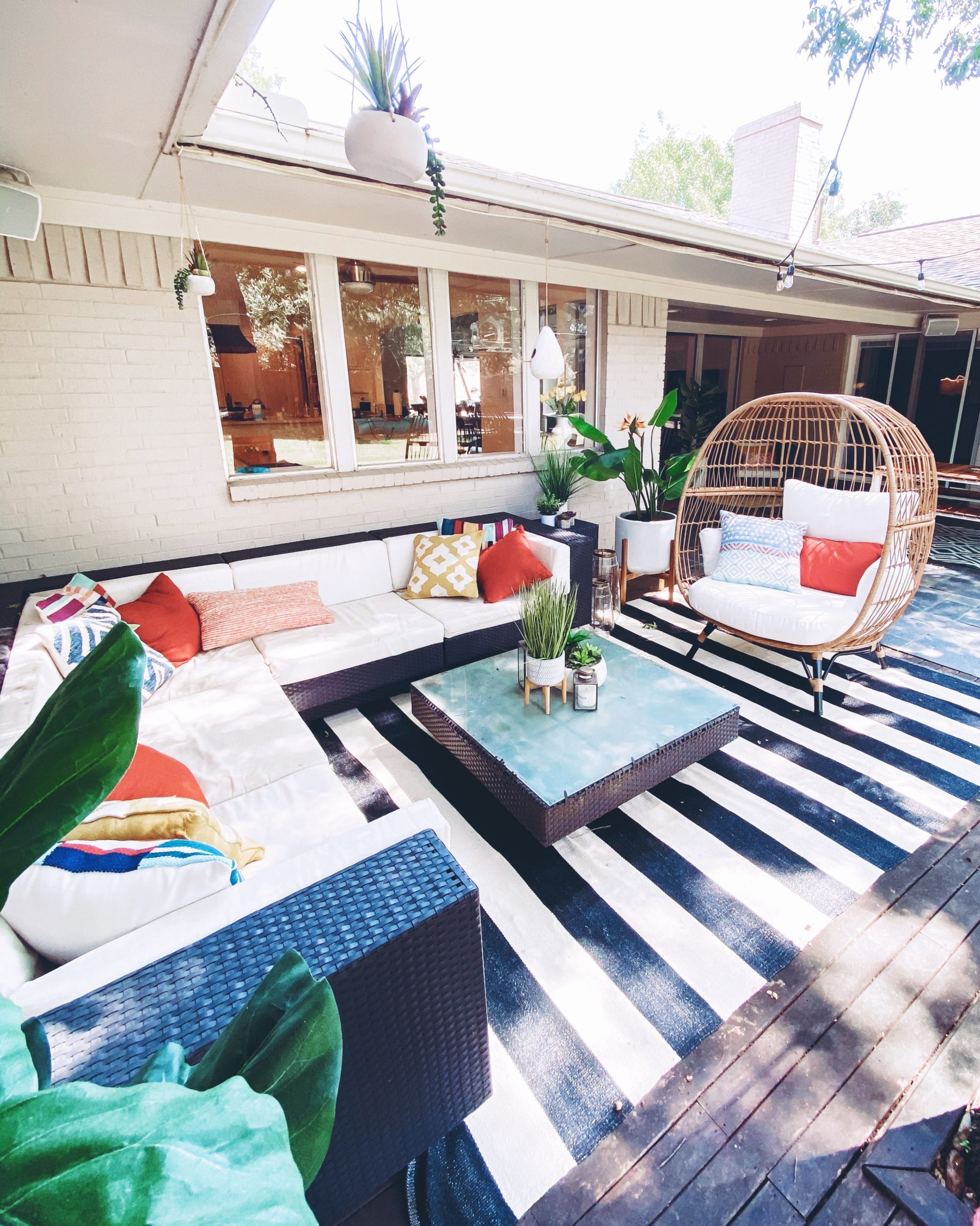 "cute & little | dallas lifestyle blog | mid-century modern outdoor patio decorating ideas | egg chair, striped rug | Mid Century Modern Backyard by popular Dallas lifestyle blog, Cute and Little: image of a backyard decorated with a Target Southport Patio Egg Chair, World Market Ceramic Sevilla Outdoor Planter, Boutique Rugs Douds Area Rug, West Elm Simple Wood Lanterns, Target Vickerman Artificial Potted Bird of Paradise Palm Tree, Pottery Barn Faux Potted Succulent in Ceramic Bowl, outdoor sectional couch and Target 12"" x 10"" Artificial Eucalyptus Plant Arrangement in Pot."