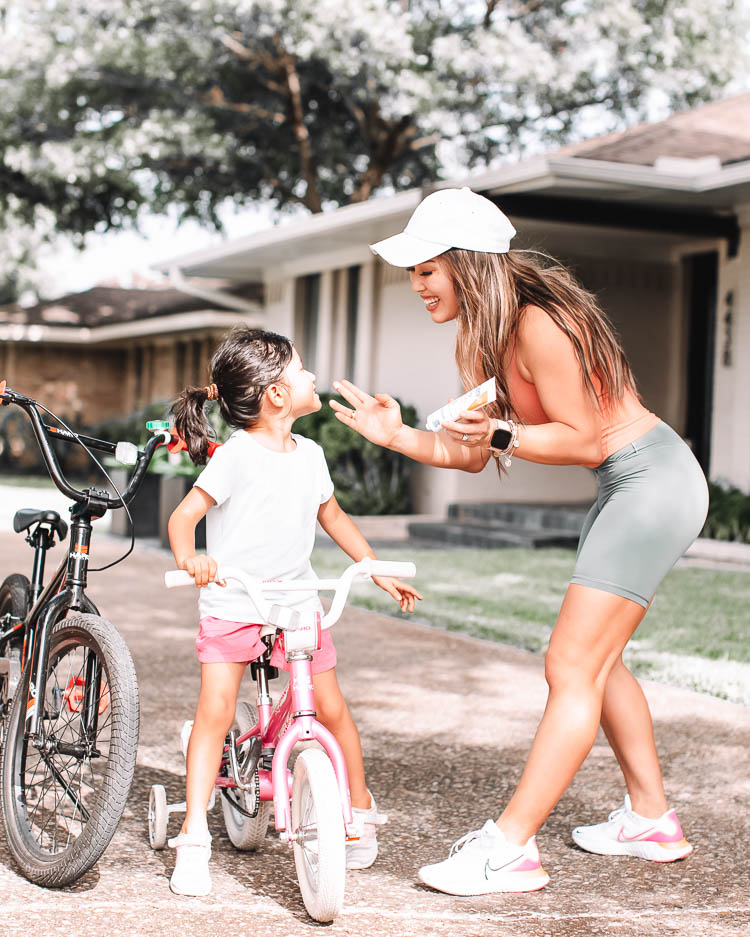 cute & little | dallas lifestyle mom blog | how to plan organize for new month | family fitness bike rides | Monthly Tasks by popular Dallas lifestyle blog, Cute and Little: image of a woman applying sunscreen to her daughter's face as she sits on her pink bike.