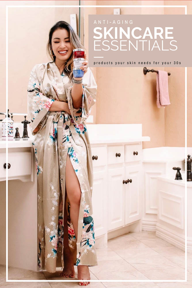 cute & little | dallas beauty skincare blog | anti-aging skincare routine for 30s | olay top drugstore skincare |   Olay Skin Care by popular Dallas lifestyle blog, Cute and Little: image of a woman standing in her bathroom and wearing a OLDSHANGHAI Women's Kimono Robe while holding jars of Olay Regenerist Micro-Sculpting Cream Face Moisturizer, Olay Regenerist Brightening Vitamin C Facial Moisturizer, and Olay Regenerist Retinol 24 Night Facial Moisturizer.