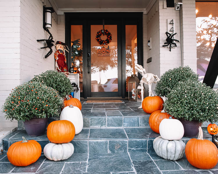 cute & little | dallas mom petite fashion blog | halloween front porch fall decor | walmart plus membership review |Walmart Halloween Decor by popular Dallas lifestyle blog, Cute and Little: image of a front porch decorated with a Walmart pumpkin wreath, pumpkin trio sign scarecrow, similar crates | similar light-up pumpkin similar 'hey pumpkin' doormat, buffalo check doormat giant spider, dog skeleton, and pumpkin pathway lights.