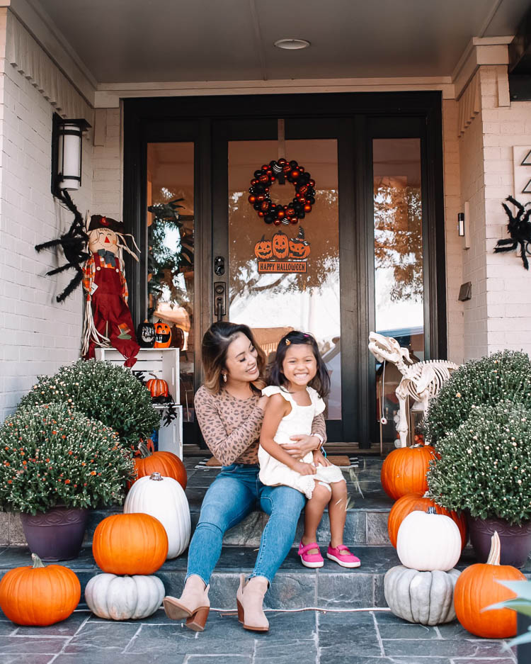 cute & little | dallas mom petite fashion blog | halloween front porch fall decor | walmart plus membership review |Walmart Halloween Decor by popular Dallas lifestyle blog, Cute and Little: image of a woman and her daughter sitting on their front porch decorated with a Walmart pumpkin wreath, pumpkin trio sign scarecrow, similar crates | similar light-up pumpkin similar 'hey pumpkin' doormat, buffalo check doormat giant spider, dog skeleton, and pumpkin pathway lights.