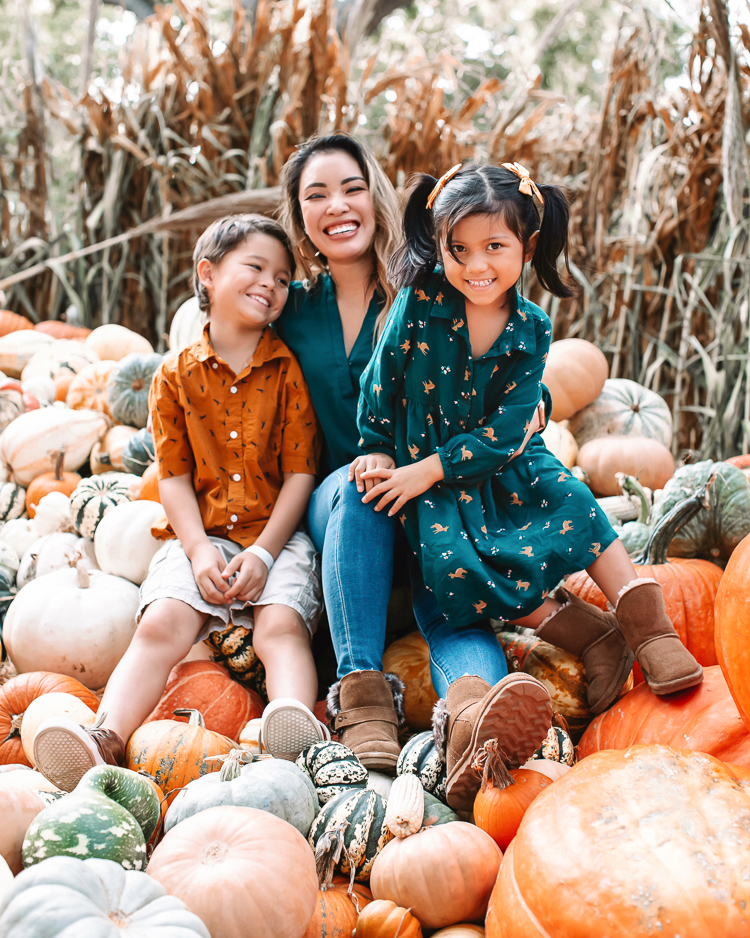 cute & little | dallas fashion blogger | fall coordinating family photo outfit ideas | dallas arboretum pumpkin patch village |Family Outfits by popular Dallas petite fashion blog, Cute and Little: image of a family sitting in a pile of pumpkins and wearing a green blouse, orange button up, brown fabric sneakers, American Eagle AE Ne(x)t Level High Waisted Jegging,BEARPAW Koko Buckle Strap Faux Fur & Genuine Sheepskin Lined Boot,Nike Killshot 2 Leather,BEARPAW Kids' Rosie Fashion Boot,The Children's Place Boys Pull-on Cargo Shorts, and green fox print dress.