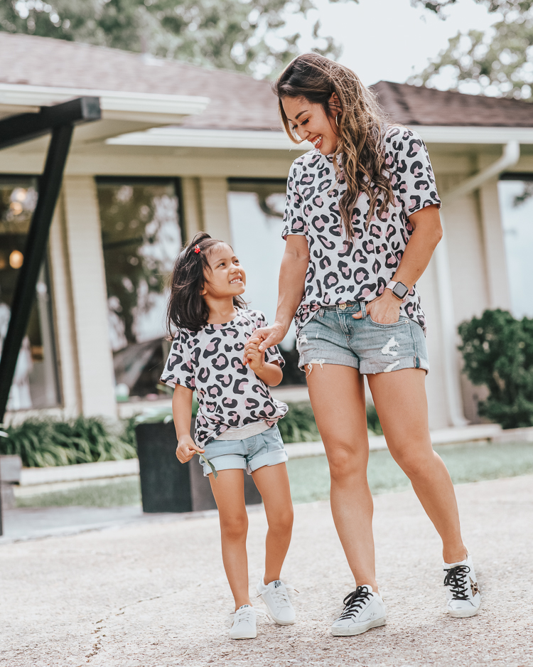 cute & little | dallas petite fashion mom blog | matching leopard shirt, jean shorts, golden goose superstar sneakers review dupes | mommy daughter matching outfits | Golden Goose Sneakers by popular Dallas petite fashion blog, Cute and Little: image of a mom and daughter wearing matching leopard print tops, Express denim shorts, GOLDEN GOOSE Superstar leather sneakers, and Amazon LanXi Girls Kids Spring Sparkle Star Bling Sequins Sneakers.