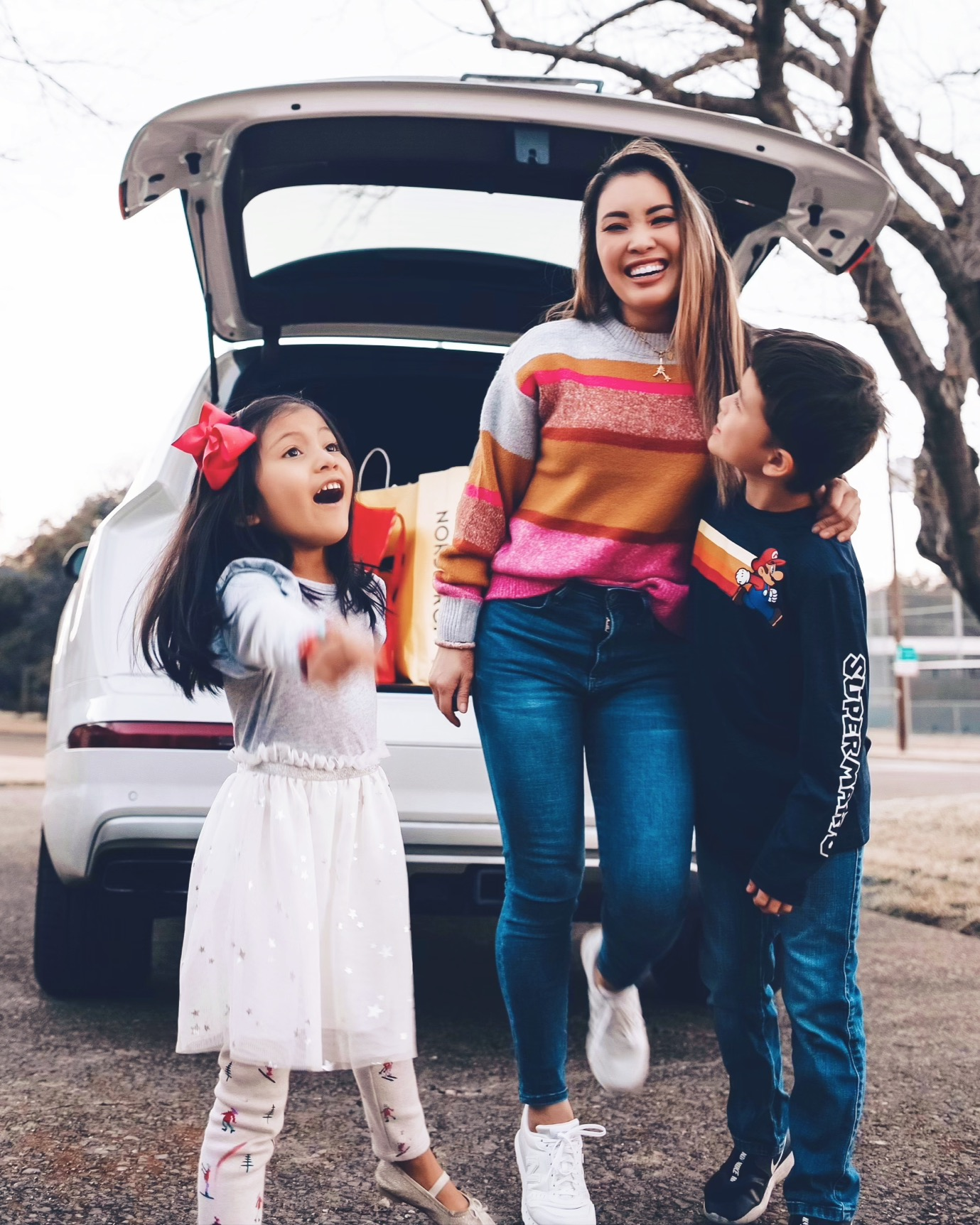 cute & little | dallas petite fashion blog | 2020 after christmas sales roundup | After Christmas Sales by popular Dallas life and style blog, Cute and Little: image of a mom and her two kids standing together behind their car and wearing aLOFT Striped Sweater, Abercrombie Jeans med wash, New Balance 311 V2 Sneakers, Sequin 'Heavenly Bodies' Horoscope Necklace,Mario shirt, Tucker & Tate jean, Nike 'Flex' sneakers, and Target dress.