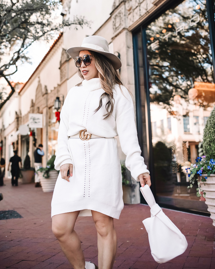 cute & little | dallas petite fashion blog | amazon winter white knit sweater dress how to style |How to Style a Sweater Dress by popular Dallas petite fashion blog, Cute and Little: image of a woman wearing a white Amazon cable knit sweater dress, white Gucci belt, white ankle boots, grey felt fedora hat and holding a white bag.