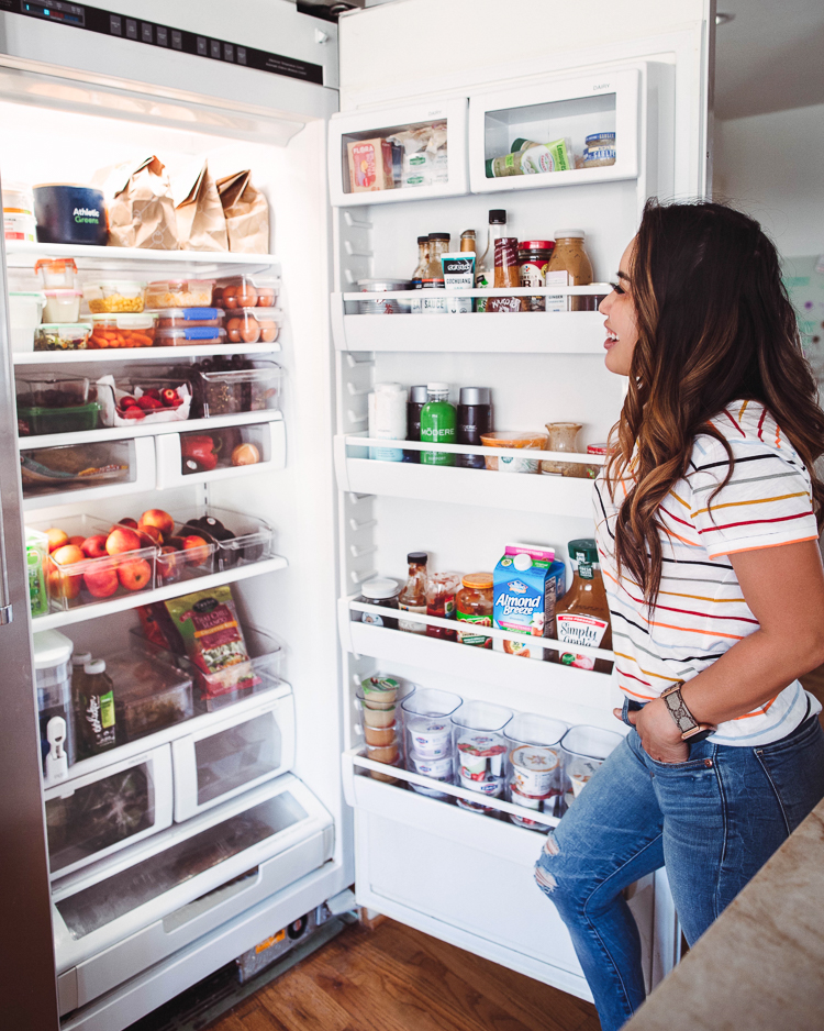 cute & little | dallas mom lifestyle blog | fridge organization tips and must-haves from walmart |Walmart Fridge Organization by popular Dallas lifestyle blog, Cute and Little: image of a woman looking in her open fridge.