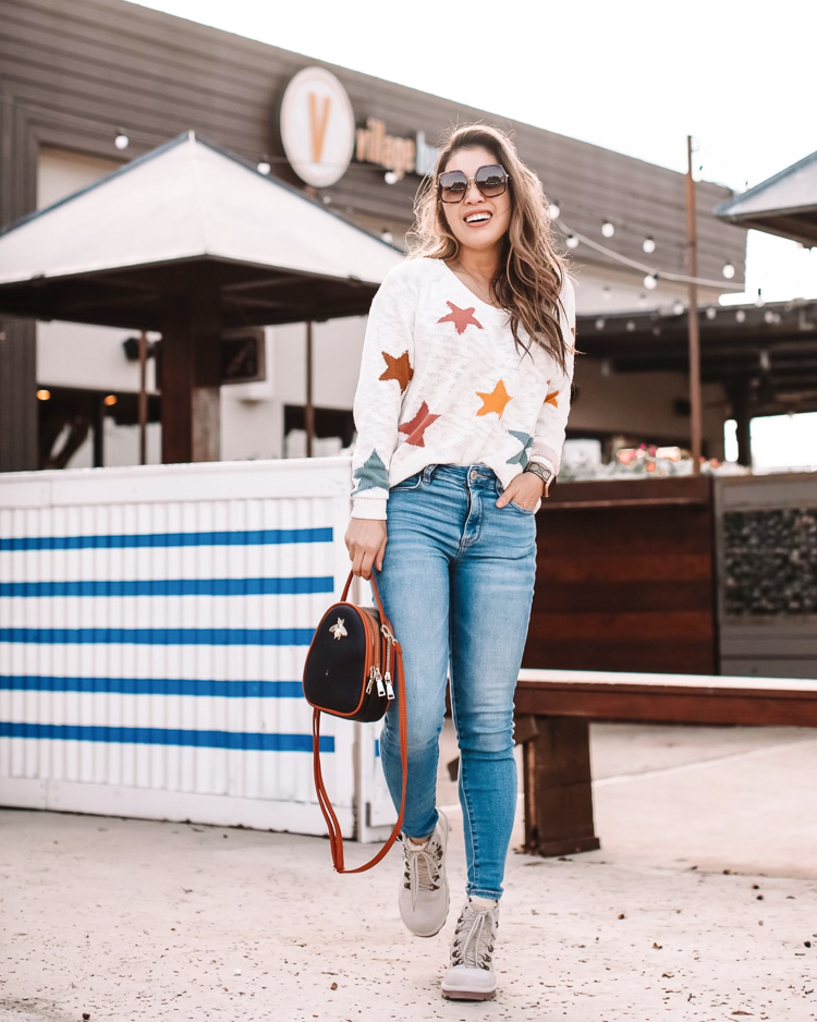 5 Lightweight Sweaters To Transition Into Spring |Lightweight Sweaters by popular Dallas petite fashion blog, Cute and Little; image of a woman wearing a Loft Lou & Grey star print sweater, jeans, and white combat boots.